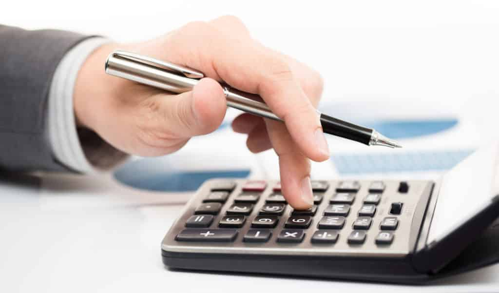 A mans hand holds a black and silver pen while punching numbers on a calculator for Mechanic's Lien