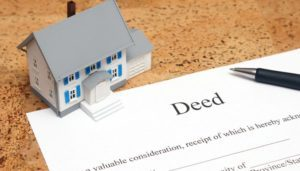 A little house and a deed document on a desk for property deed transfer