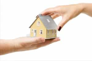 Female hand reaching for a little yellow house from male hand to transfer property deed