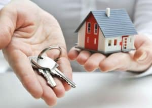 One hand holding keys and one hand holding a little house to transfer property