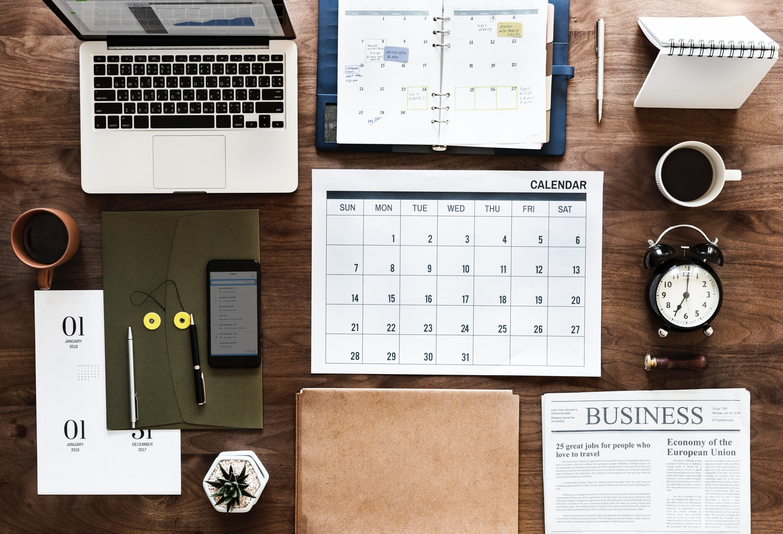 A desk seen from above with a calendar, a phone, a computer and coffee for business organizations