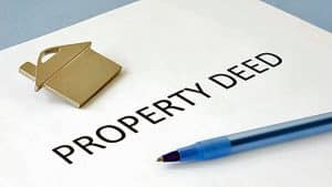 document with pen and small gold house for property deed