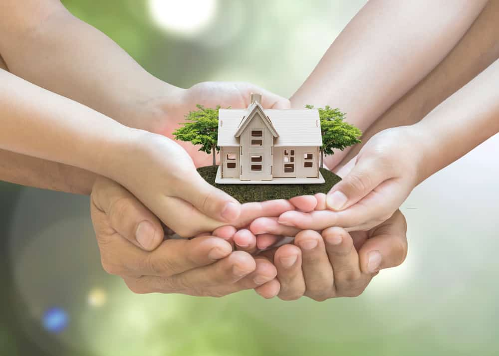 A pair of adult hands cup two pairs of children's hands while holding a small beige house with little trees behind for Affidavit of Heirship