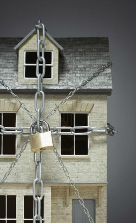 A small beige house with grey roof is surrounded by chains and a padlock for Cloud on Title