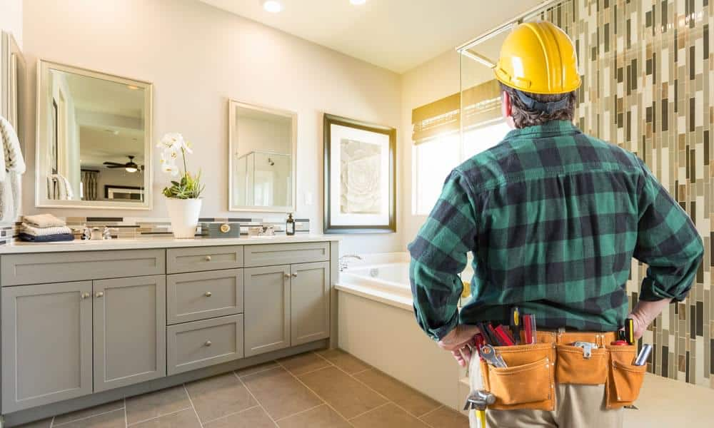 Contractor man in black and green plaid shirt and a yellow helmet stands and observes a nice bathroom for Mechanic's Lien