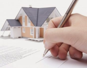 Little peach colored house with black roof is blurred in the background. Hand with pen signing a contract in the foreground for Transfer of Property Ownership.