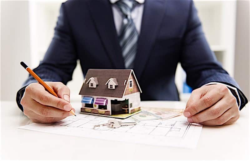 Man in blue suit has a pencil in his hand. A little brown house on top of some money. House keys in front. For setting up an LLC in Texas.