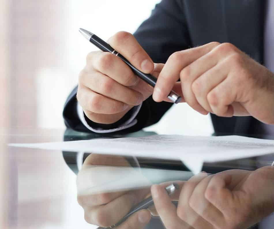 A mans hands holding a black pen over a sheet of paper on a reflective surface for Business Organizations.e