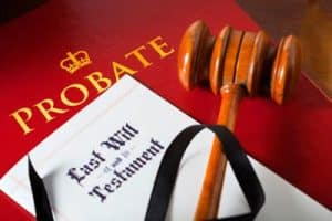 Last will and testament lays on top of a red book with the title Probate. A back ribbon and Wooden gavel lay on top for Probate a Will.